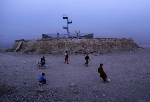 Afghan children play soccer beside an old swimming pool on a hill in Kabul