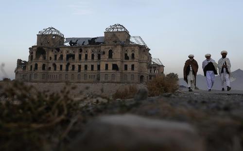 Afghan men walk past the ruins of Darulaman Palace in Kabul