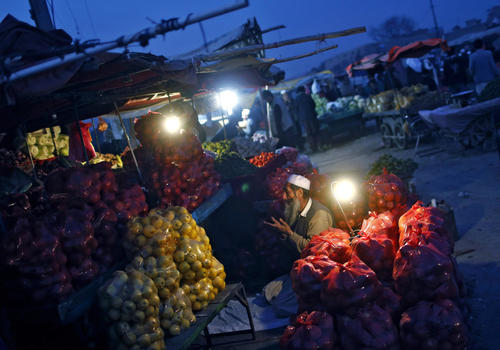 An Afghan fruit vendor performs evening prayers outside his shop at a market in Kabul