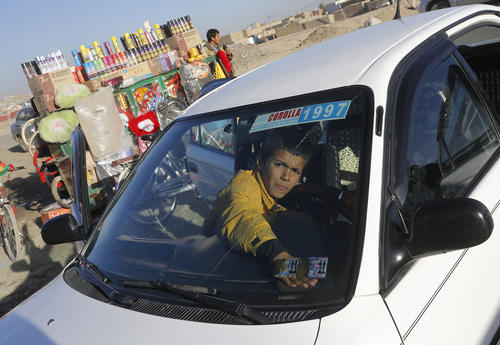 An Afghan boy cleans a car at a roadside service center in Kabul