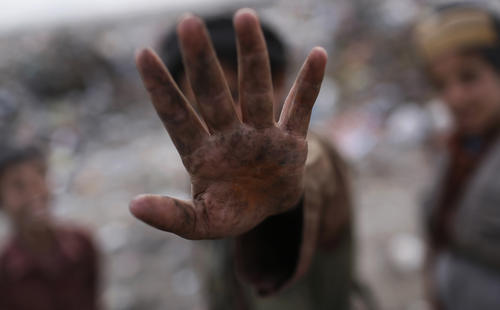 A young garbage collector blocks the camera with his hand as he avoids being pictured at a garbage dump on the outskirts of Kabul