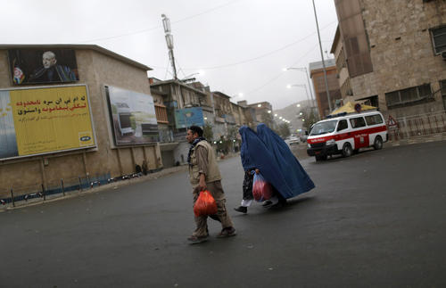 An Afghan family crosses a street in Kabul