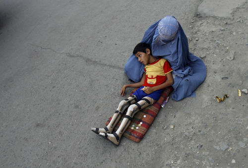 A veiled Afghan woman waits with her son, whose legs have been amputated, for alms on a street in Kabul