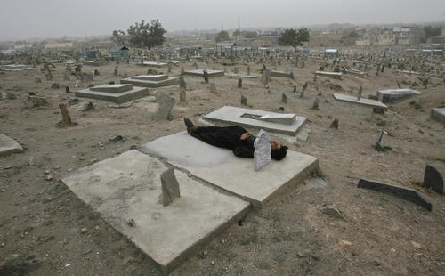 A man sleeps on a grave at a cemetery in Kabul