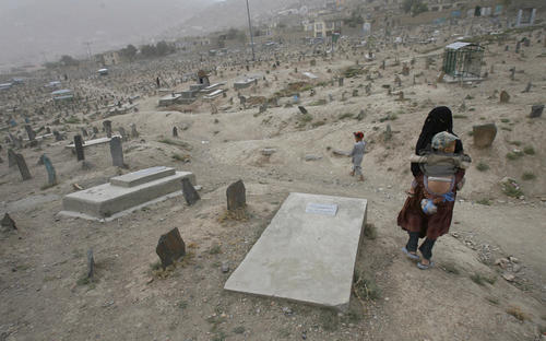 A woman carries her son on her back as she walks through a cemetery in Kabul