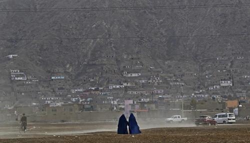 Afghan women clad in burqa walk through a playground in Kabul