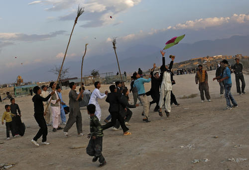 Afghan men run with long sticks to catch a falling kite on a hilltop in Kabul
