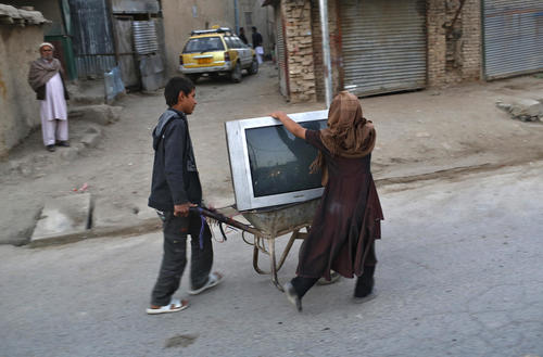 An Afghan boy and his sister transport a television on their handcart at a street in Kabul
