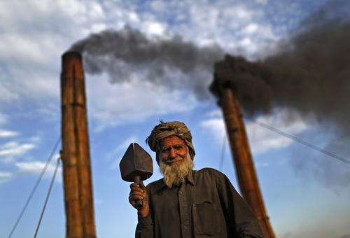 An Afghan labourer poses for a portrait at a brick-making factory outside Kabul
