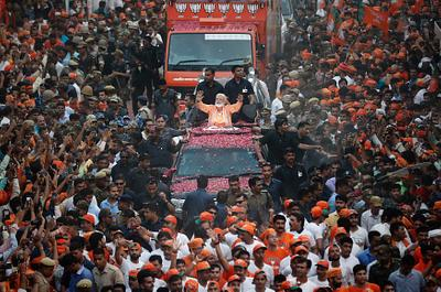 India's Prime Minister Narendra Modi waves towards his supporters during a roadshow in Varanasi