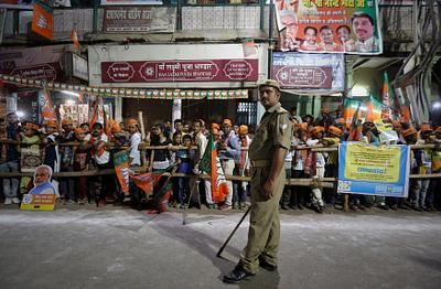 Supporters of India's Prime Minister Narendra Modi wait for his arrival as a policeman stands guard during a roadshow in Varanasi