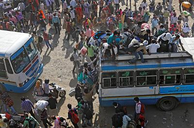 Migrant workers travel on crowded buses as they return to their villages, during a 21-day nationwide lockdown to limit the spreading of coronavirus disease (COVID-19), in Ghaziabad