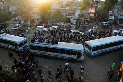 Migrant workers travel on crowded buses as they return to their villages, during a 21-day nationwide lockdown to limit the spreading of coronavirus disease (COVID-19), in Ghaziabad,