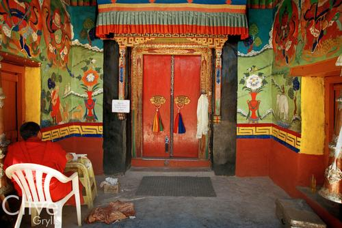 A monk sits outside the Dukhang Chenmo one of the main inner sanctums of the Hemis temple, Ladakh.