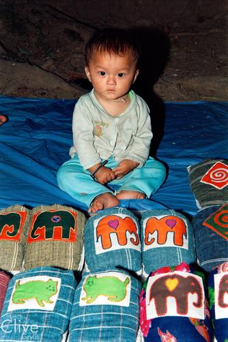 Young boy with slippers on sale in the night market, Luang Prabang.