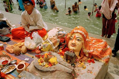 Young boy selling religious idols and icons at the Kumbh Mela festival, Madhya Pradesh.