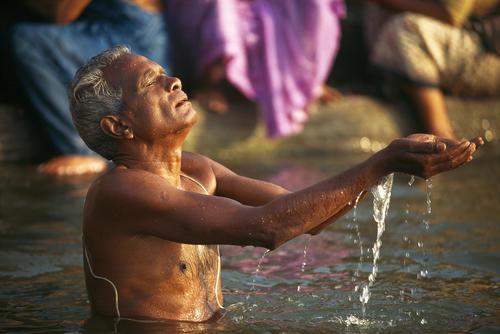Man performing a puja in the River Ganges. Varanasi, Uttar Pradesh.