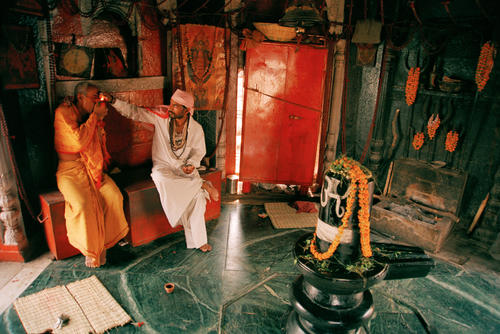 A Brahmin priest shares a ceremonial chillum in a small chapel on the Manikarnika Ghat in Varanasi. Uttar Pradesh.