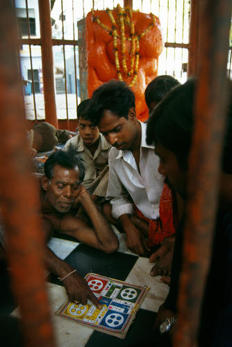Porters playing Ludo in a small chapel in Varanasi, Uttar Pradesh.