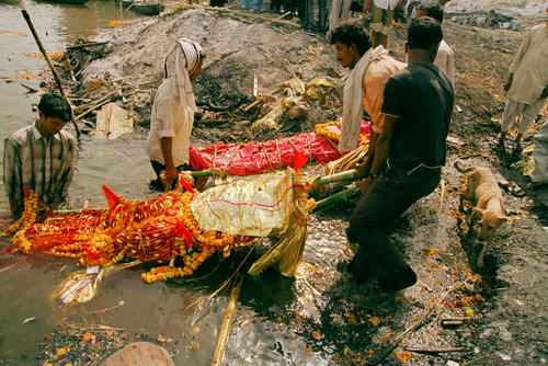 A corpse is doused in water from the River Ganges prior to cremation at the Manikarnika Ghat at Varanasi, Uttar Pradesh.