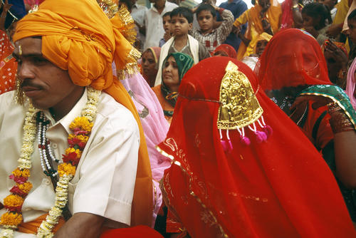 Bride and groom listening to their wedding vows at a matrimonial ceremony in Pushkar, Rajasthan.