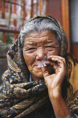 Old lady enjoying a smoke in Darjeeling, West Bengal.