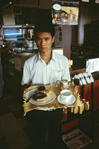 A waiter at the Glenary's bakery and restaurant on the Mall, Darjeeling, West Bengal.