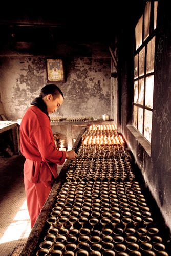 Monk lighting butter lamps at the Dali Gompa just one of many monasteries close to Darjeeling in West Bengal.