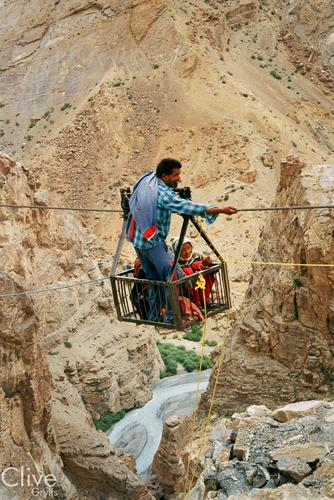 People using a rope bridge to cross a gorge at Kibber in the Spiti Valley, Himachal Pradesh.