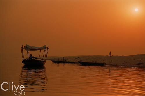 Boat silhouetted in early morning light on the River Ganges, Varanasi, India.
