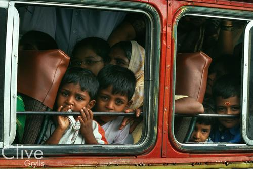 Children peering out of a crowded bus in Delhi.