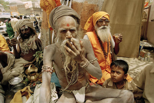 Sadhus or holy men and a child enjoying tea and a smoke at the Kumbh Mela festival held in Ujjain, Madhya Pradesh.