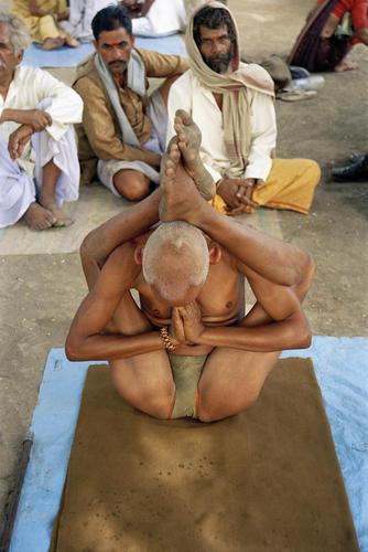 Man performing early morning yoga at the Kumbh Mela festival, Ujjain, Madhya Pradesh, India