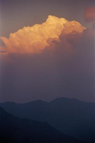 A sunset lights up cloud formations overlooking the Makaibari Tea Estate, Kurseong, West Bengal, India