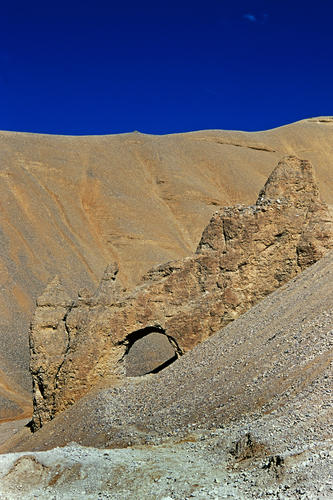 An arched natural gateway dominates the landscape near the settlement of Pang, Ladakh.