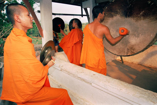 Monks performing on traditional instruments to announce prayers at the Wat Thammothayalan temple complex, Mount Phousi, Luang Prabang, Laos.