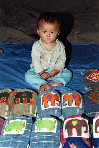 Young boy with slippers on sale in the night market, Luang Prabang, Laos.