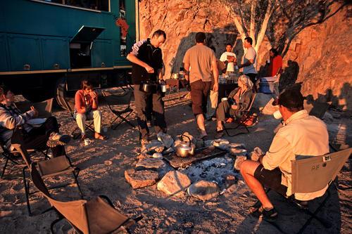 Tourists enjoying tea at a desert camp at Twyfelfontien, Namibia.