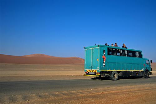 Overlanding bus passing through the Namid desert close to Sossusvlei, Namibia.