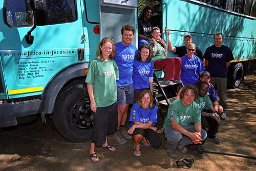 Tourists lined up for a photo call outside their overlanding bus, Namibia.