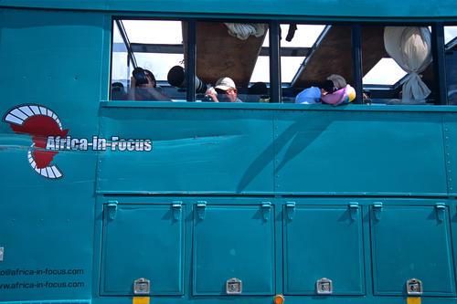 Tourists taking pictures from their overlanding bus at Lake Nukuru, Kenya.