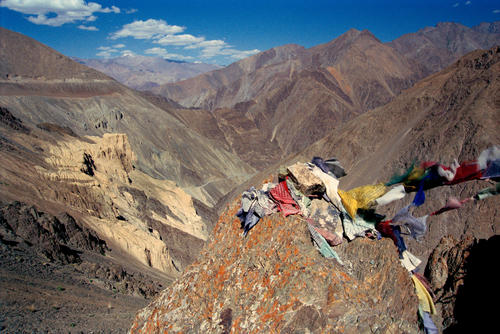Prayer flags flutter in the breeze on an outcrop overlooking the lunar-like rock formations close to Lamayuru, Ladakh.