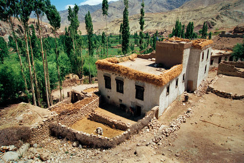 A typical Ladakhi house with carved lintels and grass and firewood stacked on the roof.