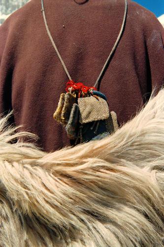 Traditional wool clothing and ornamental bags adorn a lady at the Lamayuru temple, Ladakh.