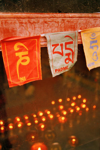 Butter lamps being reflected through a window at the Likir temple, Ladakh.