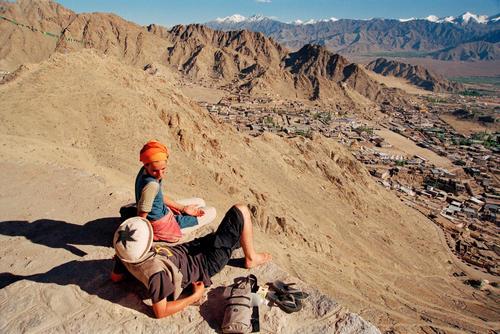 Tourists sitting on a ridge overlooking Leh, Ladakh.