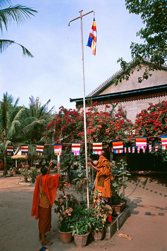 Monks hoisting up a flag at the Angkor Wat temple complex, Siem Reap.