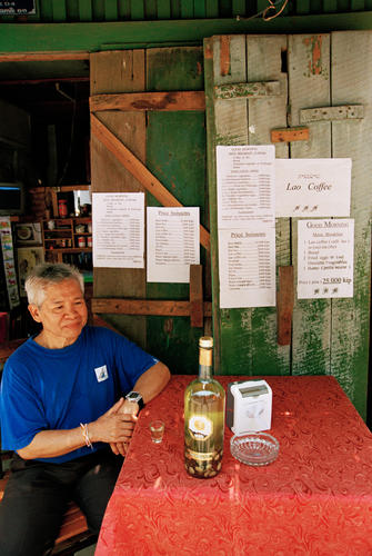 Man drinking traditional Lao whisky outside a café at Luang Prabang.