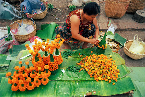 Women making floral decorations at the morning market, Luang Prabang.