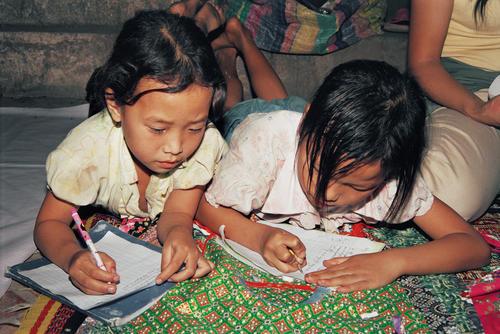 Young girls doing their homework at the night market, Luang Prabang.